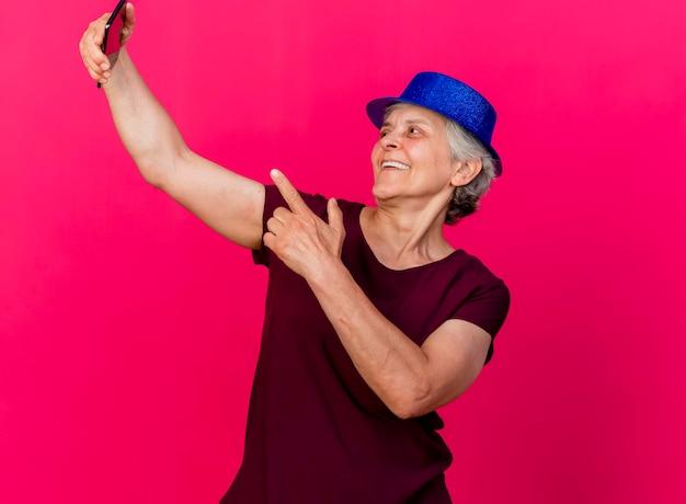 Blije oudere vrouw met feestmuts kijkt en wijst naar de telefoon op roze