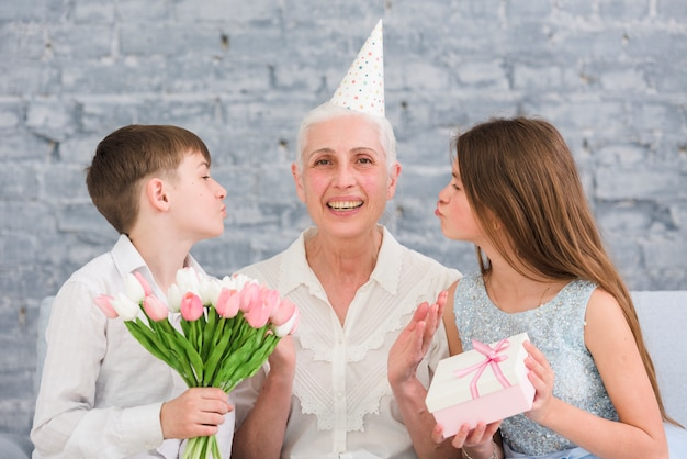 Blije oudere vrouwenzitting binnen - tussen haar kleinkinderen met bloemenboeket en giftdoos