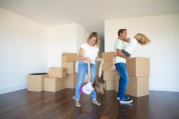 Blije ouders en kinderen die genieten van een nieuw huis, dansen en plezier maken in de buurt van hopen dozen in de lege ruimte