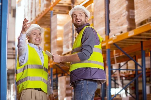 Blije positieve mannen die glimlachen terwijl ze genieten van het samenwerken