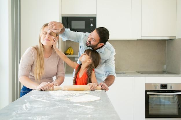 Blije positieve moeder, vader en meisje die gezichten met bloempoeder kleuren tijdens het samen bakken.