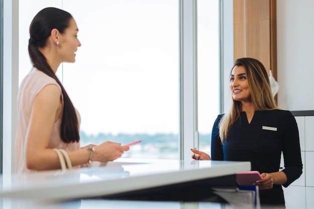 Blije positieve vrouw die lacht naar de klant terwijl ze bij de receptie staat