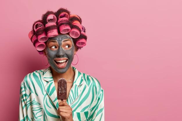 Blije positieve vrouw draagt haarrollers voor krullen en schoonheidsmasker, eet heerlijk chocolade-ijs, draagt casual gewaad, kijkt vrolijk opzij, geïsoleerd op roze, lege kopie ruimte.