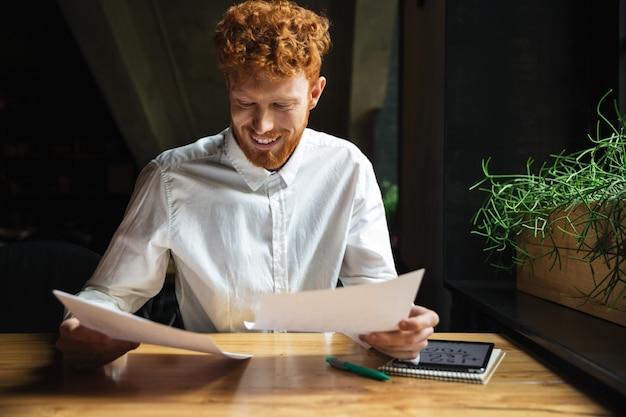 Blije readhead jonge mens in wit overhemd die met documenten thuis werken