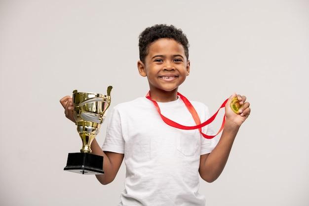 Blije schattig gemengd ras kleine jongen met medaille en gouden beker in handen