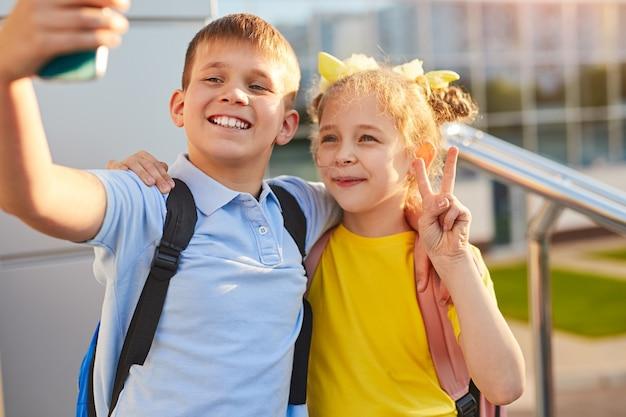 Blije schoolkinderen die selfie op straat maken