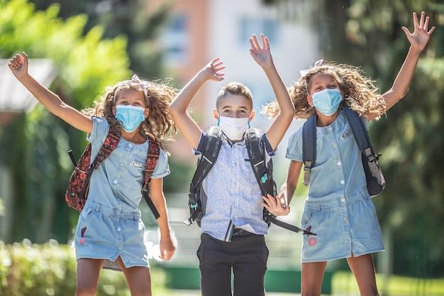 Blije schoolkinderen met gezichtsmaskers springen van vreugde om terug te keren naar school tijdens de covid-19-quarantaine.