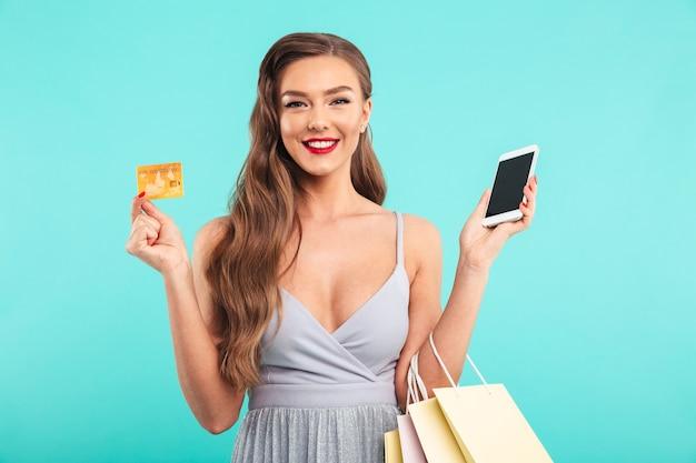 Blije shopaholic vrouw poseren boodschappentassen en met smartphone en creditcard, geïsoleerd over blauwe muur
