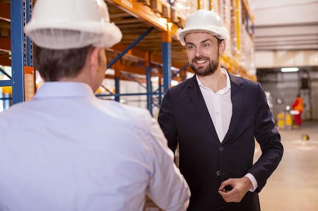 Blije slimme zakenman die zijn magazijnmanager bekijkt terwijl hij hem begroet
