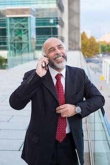 Blije succesvolle rijpe zakenman die op cellphone spreekt
