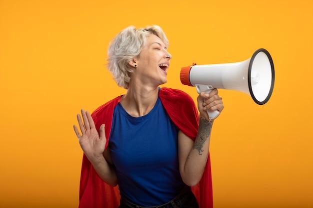 Blije supervrouw met rode cape houdt luide spreker die op oranje muur wordt geïsoleerd