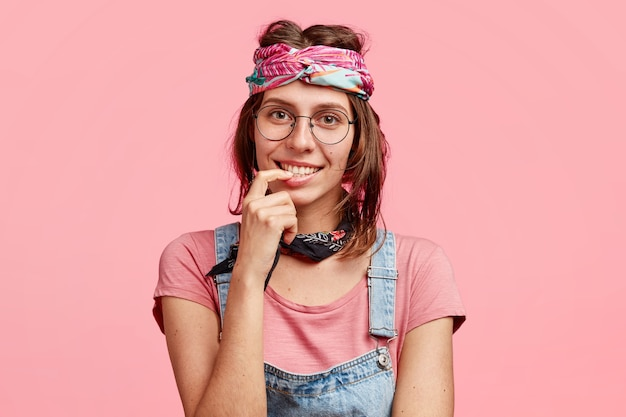 Blije tevreden hippievrouw met zachte glimlach, ontmoet vriend, heeft een aangenaam gesprek, draagt stijlvolle bandana op het hoofd, geïsoleerd over roze muur