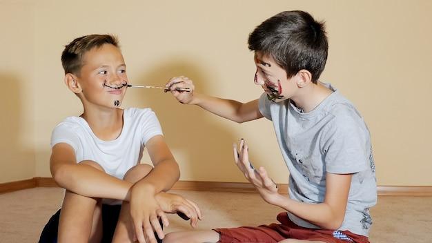 Blije tevreden jongens die plezier hebben en tekenen met penseel op gezicht zittend op de vloer
