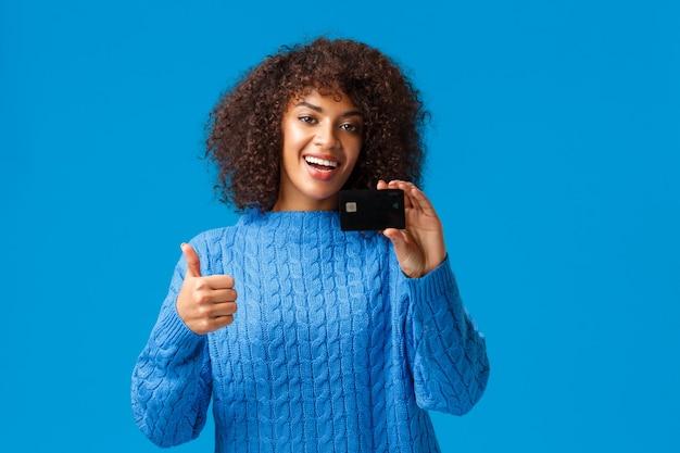 Blije, tevreden klant raadt bank aan. aantrekkelijke moderne jonge afro-amerikaanse vrouw in de winter trui alles kopen met creditcard