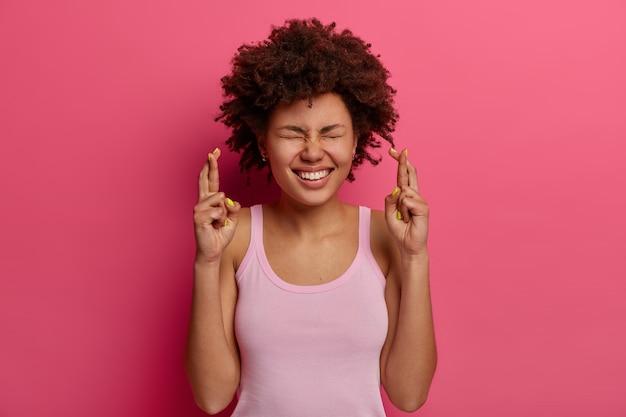 Blije, tevreden schattige vrouw staat met gekruiste vingers, wil een droom die uitkomt, gelooft in geluk, draagt een casual vest, doet een wens, wacht op positief antwoord of goed nieuws, staat hoopvol binnen.