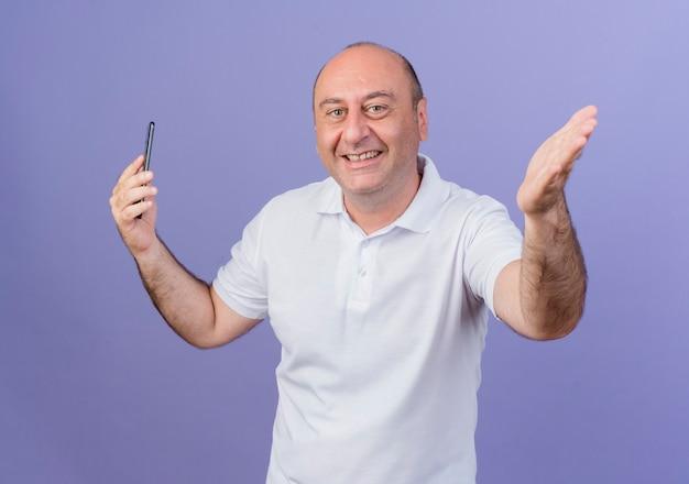 Blije toevallige volwassen zakenman die camera bekijkt die mobiele telefoon houdt en uit hand uitrekt die op purpere achtergrond wordt geïsoleerd