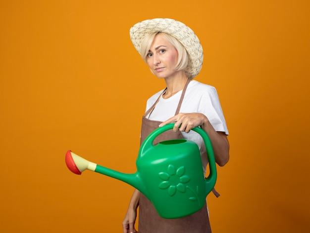 Blije tuinmanvrouw van middelbare leeftijd in tuinmanuniform met hoed in profielweergave met gieter geïsoleerd op oranje muur met kopieerruimte