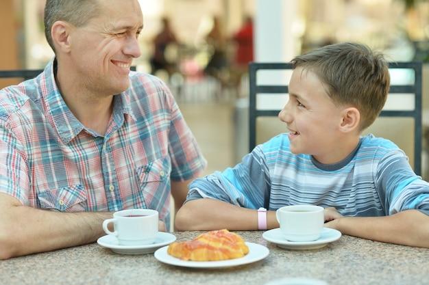 Blije vader met zoon bij het ontbijt op tafel