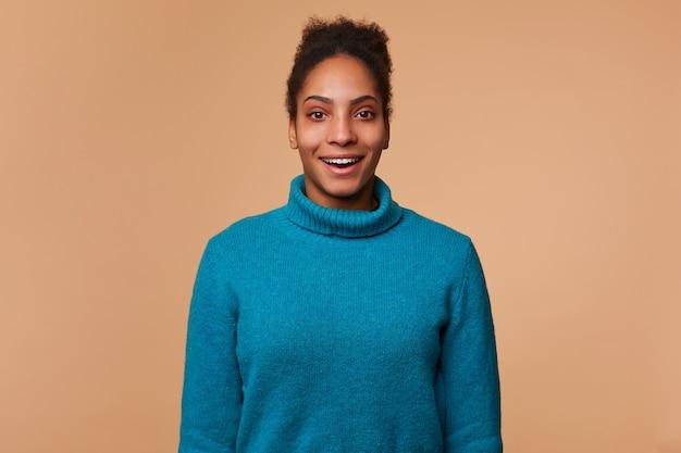 Blije verbaasde afro-amerikaanse dame in een blauwe trui, met donker krullend haar, hoorde over gekke korting. glimlachen en geïsoleerd kijken.