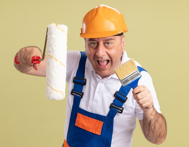 Blije volwassen bouwersmens houdt rolborstel en verfborstel die op olijfgroene muur wordt geïsoleerd
