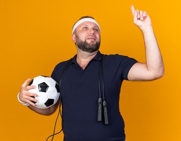 Blije volwassen slavische sportieve man met touwtjespringen om de nek met hoofdband en polsbandjes die bal vasthouden en omhoog wijst geïsoleerd op oranje muur met kopie ruimte