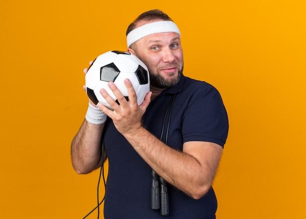 Blije volwassen slavische sportieve man met touwtjespringen om de nek met hoofdband en polsbandjes met bal geïsoleerd op oranje muur met kopie ruimte