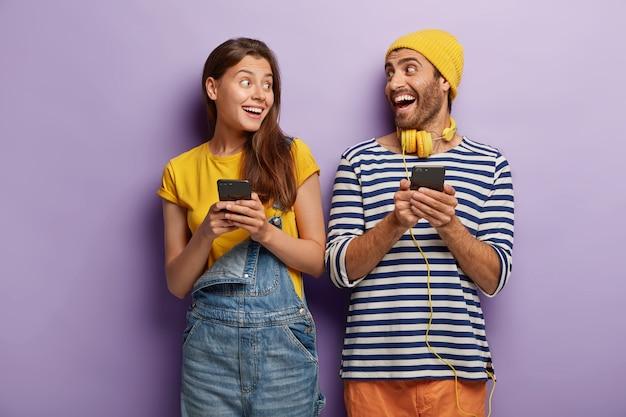 Blije vriend en vriendin lachen en kijken elkaar aan, houden mobiele telefoons vast