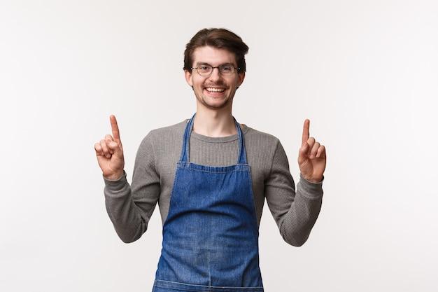 Blije, vriendelijk ogende barman nodigt zijn bezoek uit, wijst met zijn vingers omhoog en lacht vrolijk naar de camera terwijl hij een schort draagt op het werk, koffie zet voor de klant, stoelen boven toont,