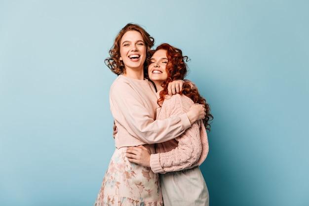 Blije vrienden die op blauwe achtergrond omhelzen. opgewonden meisjes die glimlachen en goede emoties uiten.