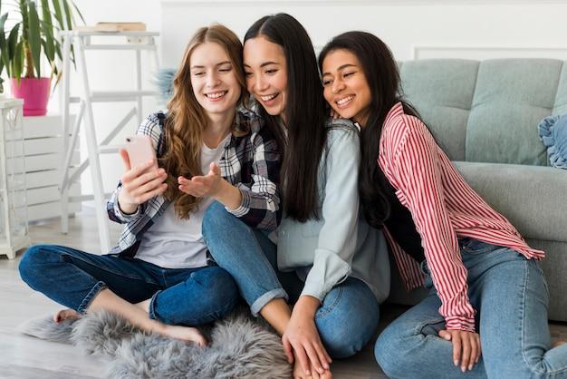 Blije vrienden die selfie op smartphone nemen