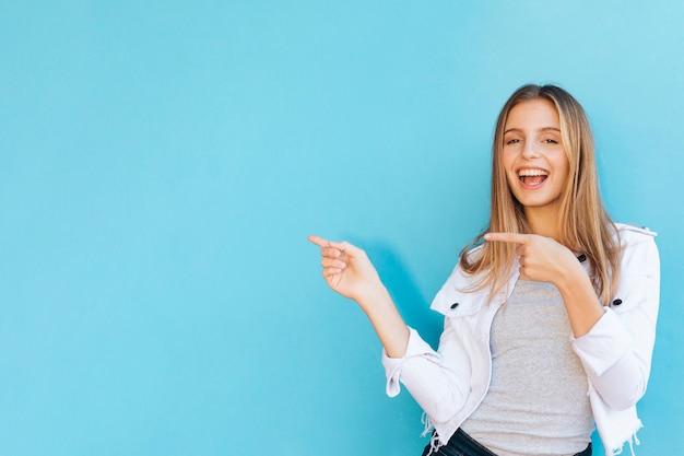 Blije vrij jonge vrouw die haar vingers richt tegen blauwe achtergrond