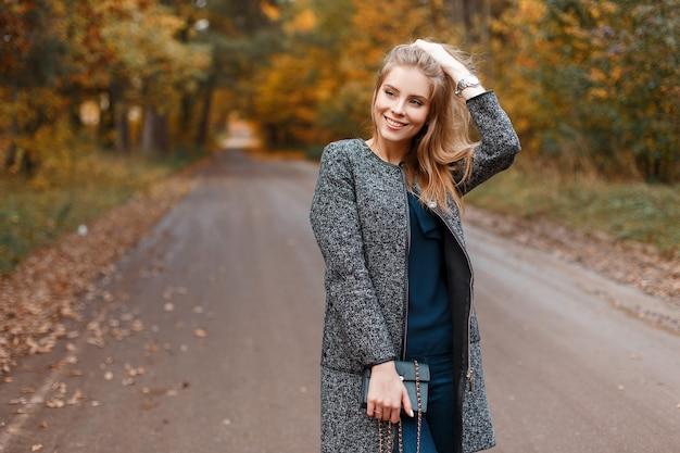 Blije vrij mooie jonge vrouw met trendy grijze vacht