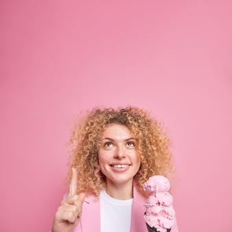 Blije vrolijke, gekrulde jonge europese vrouw die hierboven geconcentreerd is, geeft aan dat op lege kopieerruimte heerlijk kegelijs vasthoudt, demonstreert reclame-inhoud, eet zomerdessert tijdens het weekend