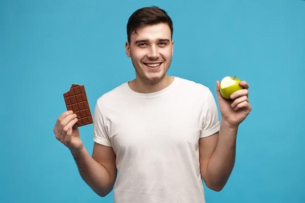 Blije vrolijke jonge donkerharige kerel die camera met brede opgewekte glimlach bekijkt die half gebeten groene appel houdt