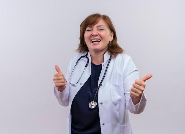 Blije vrouw arts die op middelbare leeftijd medische kleed en stethoscoop draagt die duimen op geïsoleerde witte muur met exemplaarruimte tonen