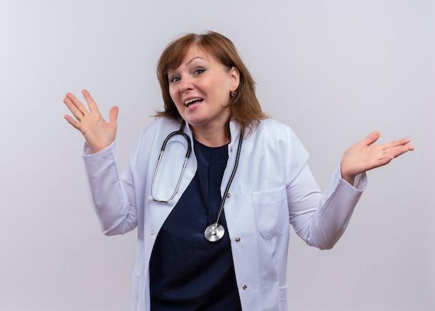Blije vrouw arts die op middelbare leeftijd medische mantel en stethoscoop draagt die lege handen op geïsoleerde witte muur tonen