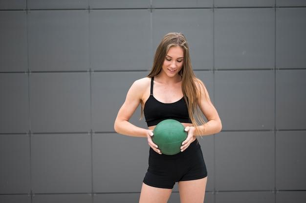 Blije vrouw die een middelgroot schot van de geschiktheidsbal houdt