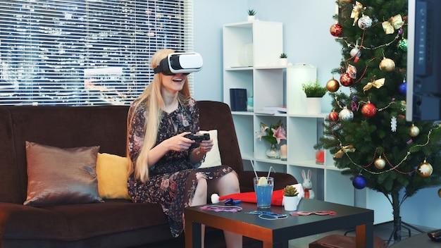 Blije vrouw die een spel met bedieningshendel in virtuele werkelijkheidsglazen speelt voor tv op kerstmis