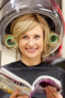Blije vrouw die een tijdschrift met haarkrulspelden leest onder een hairdryer