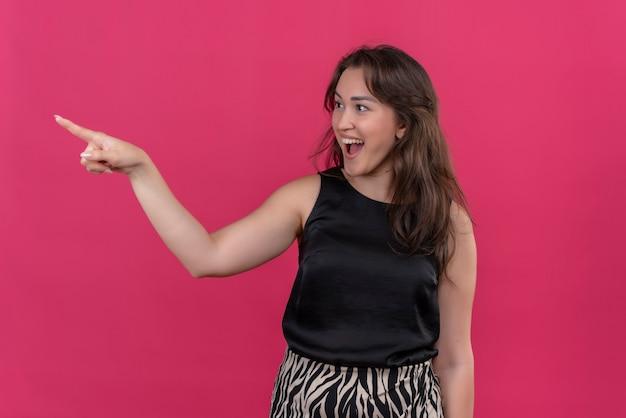 Blije vrouw die een zwart hemd draagt, wijst naar de zijkant op roze muur