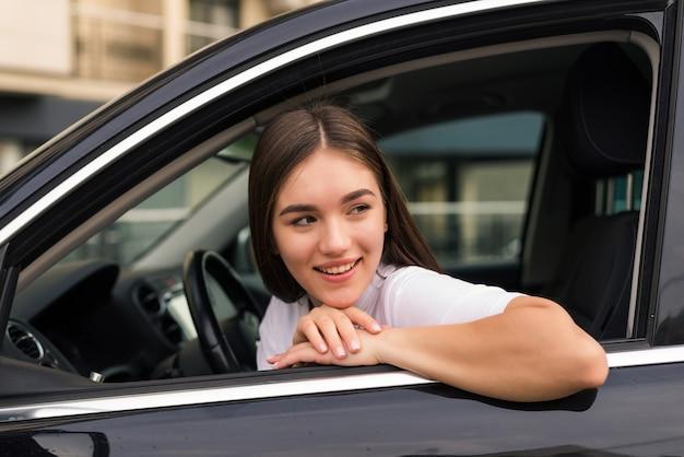 Blije vrouw die haar elleboog over autoraam leunt terwijl zij geniet van road trip