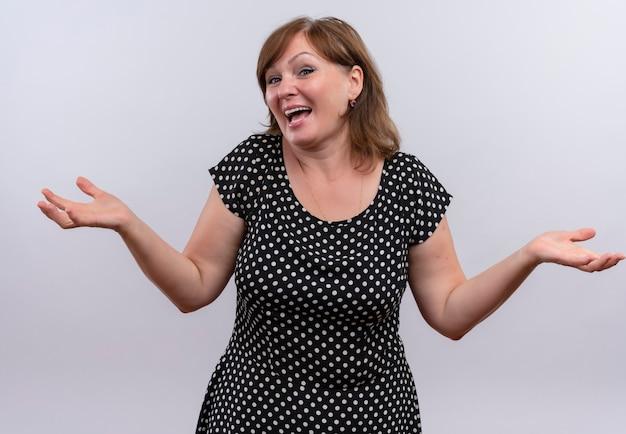 Blije vrouw die op middelbare leeftijd lege handen op geïsoleerde witte muur toont