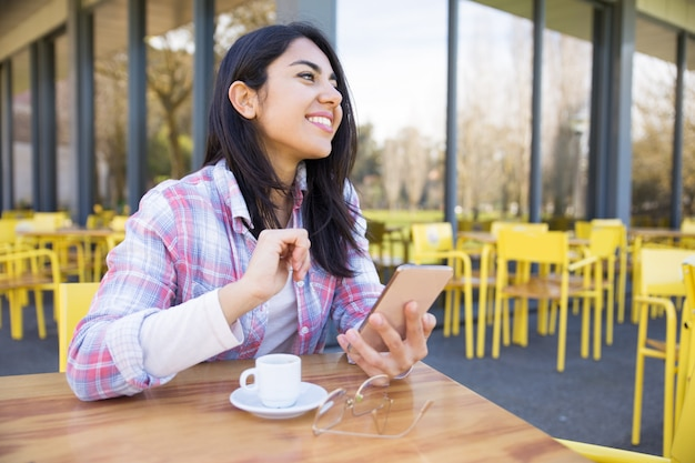 Blije vrouw gebruikend smartphone en drinkend koffie in koffie