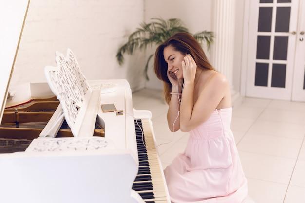 Blije vrouw in een roze kleding die aan muziek in de telefoonhoofdtelefoons luisteren die bij de piano zitten