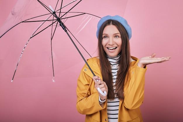 Blije vrouw in geel regenjasje met paraplulach