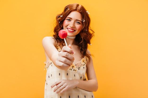Blije vrouw in gele zomerjurk houdt roze snoep. portret van vrouw met bloemen in haar haar op oranje achtergrond.