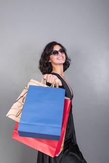 Blije vrouw in het zwart met geschenkdozen