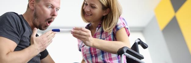Blije vrouw in rolstoel toont verraste man zwangerschapstest