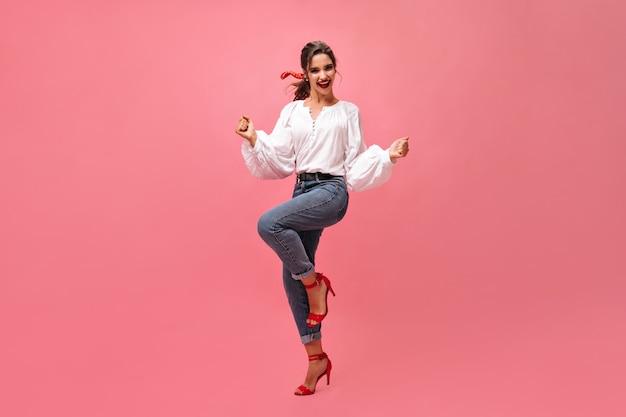 Blije vrouw in spijkerbroek, witte blouse die op roze achtergrond danst. modern meisje met rode lippenstift en in stijlvolle hakken verheugt zich op geïsoleerde achtergrond.