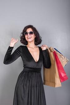 Blije vrouw in zwarte jurk met kleurrijke boodschappentassen